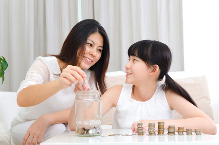Asian girl and mother putting coins into glass bottle. Money saving concept.