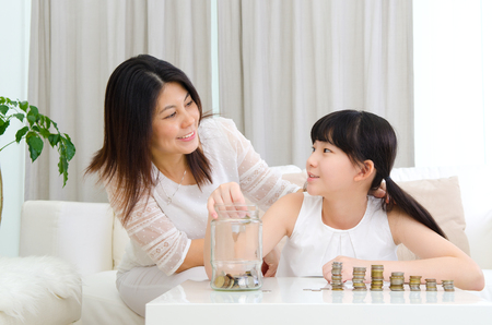 Asian girl putting coins into the glass bottle. Money saving concept.