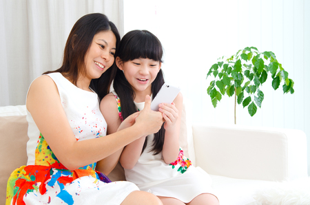 on the handphone: Beautiful asian woman and daughter having fun playing smartphone