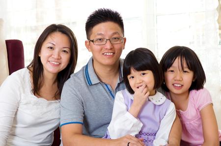 Retrato de interior de la familia asiática que mira la cámara photo