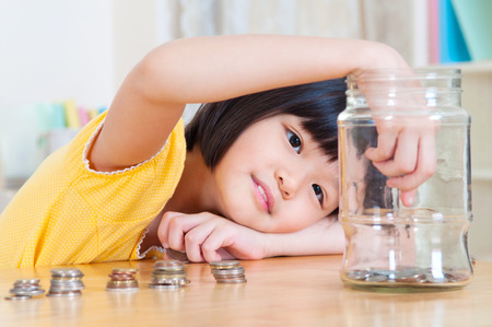 Asian child putting coins into glass bottle. Money saving concept.