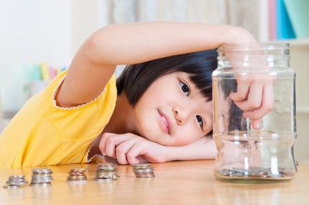 Bambino asiatico mettere le monete in bottiglia di vetro. Denaro concetto di risparmio. Archivio Fotografico