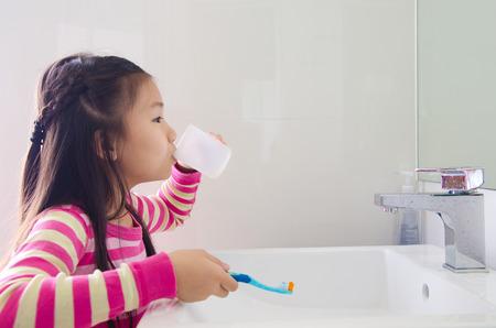 Preciosa niña asiática enjuague la boca después de cepillarse los dientes Foto de archivo