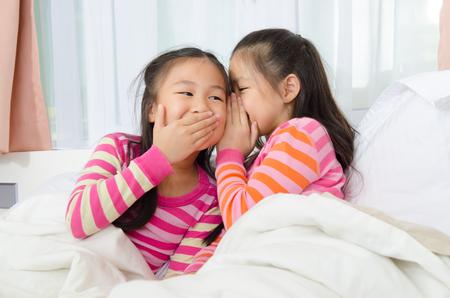 niños chinos: muchachas asiáticas linda que susurra en la cama