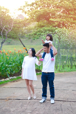 Asian pregnant woman walking in the park together with husband and daughter