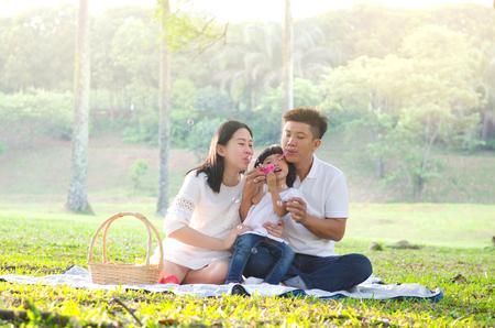 Asiatische Familie spielt Blase im Park Standard-Bild - 57265585