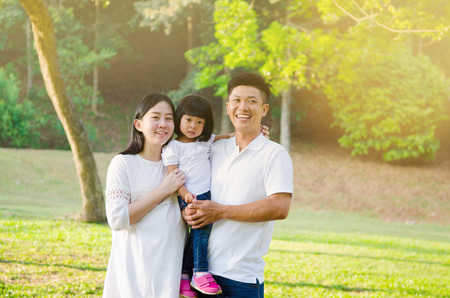 Asian family enjoying outdoor nature in the park Фото со стока