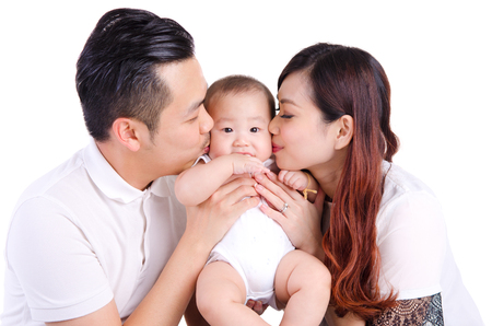Asian parent kiss their six months old baby boy Stock Photo