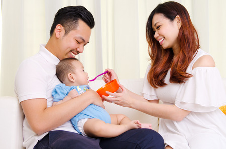 Asian mother feeding her six months old baby with solid food Standard-Bild