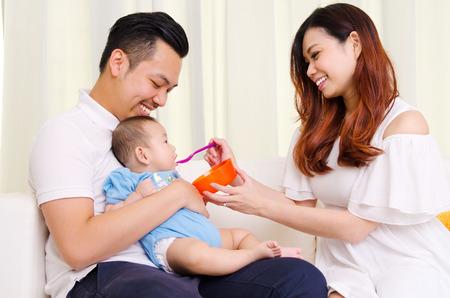 Madre asiatica che alimenta i suoi sei mesi di età bambino con il cibo solido
