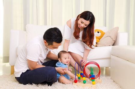 アジアの親が彼らの 6 ヶ月の男の子と遊ぶ