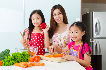 enjoyed: Asian mother and daughters enjoyed cooking in the kitchen Stock Photo