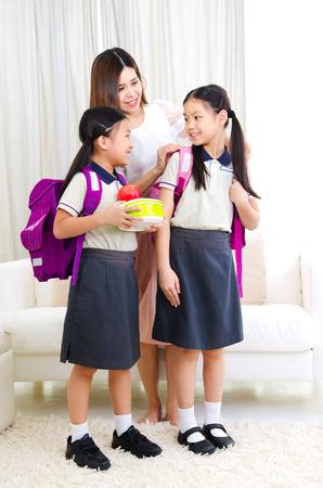 Asian mother get her daughters ready to school Standard-Bild