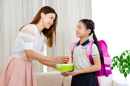 Asian mother get her daughter ready to school