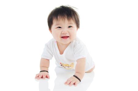 Alegre arrastre asiático bebé en el suelo