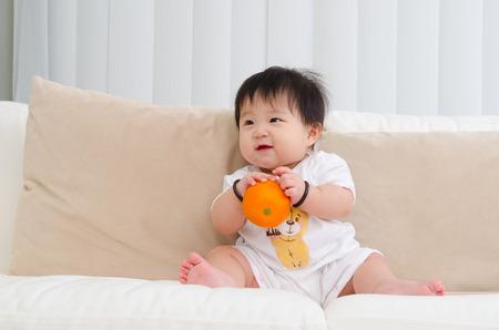 bebe sentado: Bebé asiático que sostiene una naranja