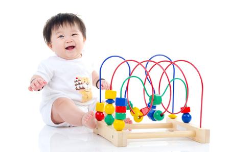 bebe sentado: bebé asiático que se sienta en el suelo y que juega el juguete