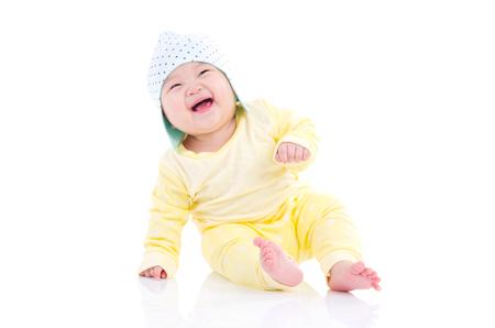 Bébé asiatique assis sur le sol et rire
