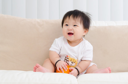 baby sitting: Asian baby sitting on sofa