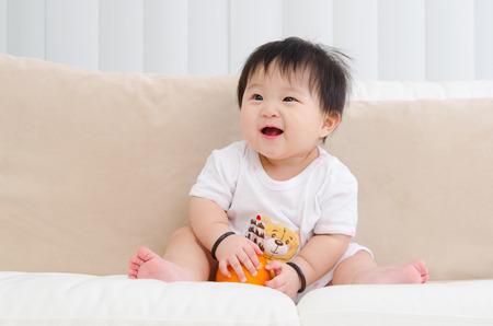 bebe sentado: bebé asiático que se sienta en el sofá