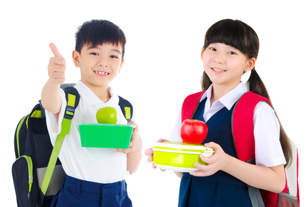 child smile: Asian primary school girl holding lunch box. Healthy eating concept for schoolchild. Stock Photo