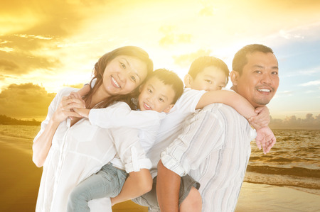 asian family outdoor: Asian family relaxed at beachside in the beautiful sunset Stock Photo