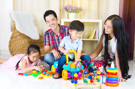 Asian family playing toys in the living room