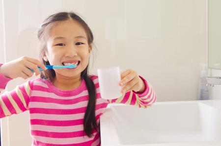 사랑스러운 아시아 어린이 욕실에서 치아를 칫 솔 질