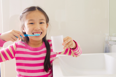 Lovely asian child brushing teeth in the bathroom