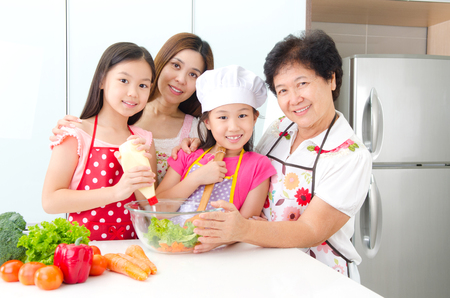 Asian three generations family prepared salad in the kitchen