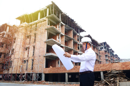 Asian engineer looking at the blueprint at building construction site