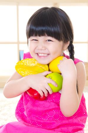 Asian girl holding fruits Фото со стока
