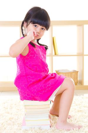 Lovely asian girl sitting on books
