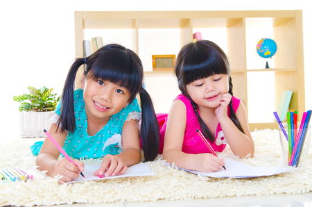 Asian children drawing pictures with color pencils