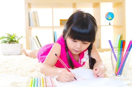 Asian girl drawing picture with color pencil