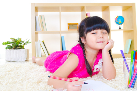 Asian child drawing picture with color pencil Фото со стока