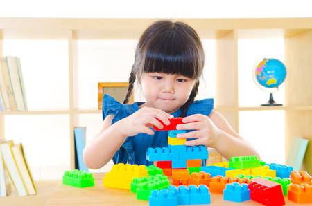 Asian girl playing building blocks
