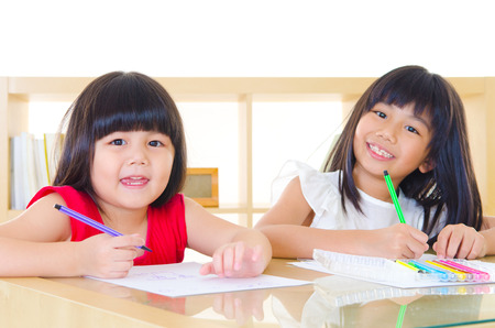 Asian kids drawing picture with color pencils Фото со стока