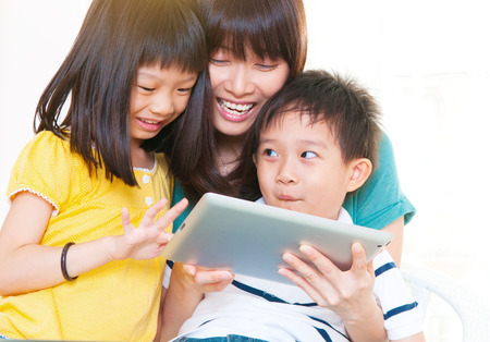 Asian mother and kids using tablet computer