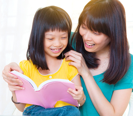 Asian mother and daughter reading book together