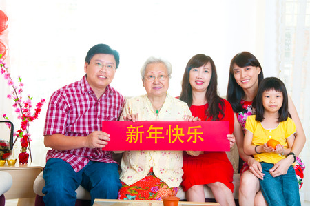Asian family holding red banner with chinese word