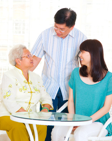 Asian senior woman having conversation with son and daughter