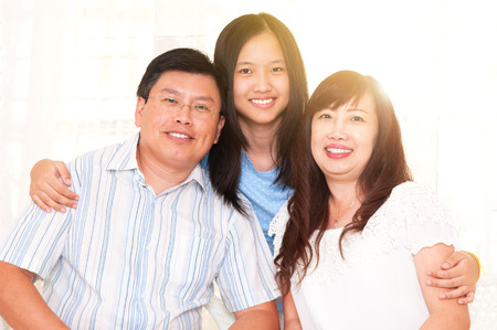 Asian middle aged couple and their teenage daughter Фото со стока
