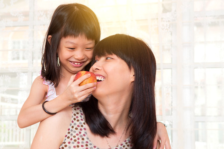 Asian child feeding mother with apple