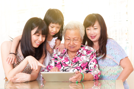 Asian three generations having fun with tablet computer