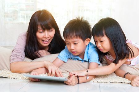Asian mother and kids having fun with tablet computer
