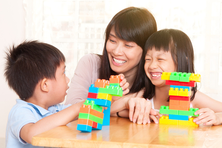 Asian woman and kids playing building blocks