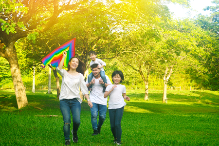 Outdoor portrait of asian parent flying kite and kids