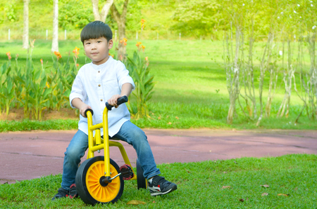Lovely asian boy cycling in the park