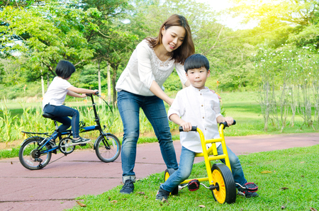Asian mother and kids having fun at the park